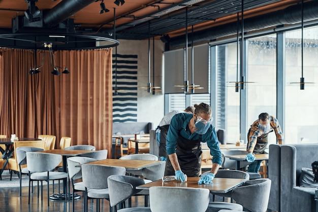 Camerieri nei tavoli di pulizia degli indumenti da lavoro protettivi nel ristorante
