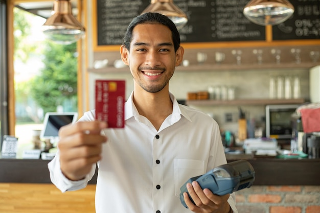 Il cameriere accetta una carta di credito per il pagamento Foto Premium