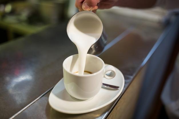 Cameriere che aggiunge latte al caffè
