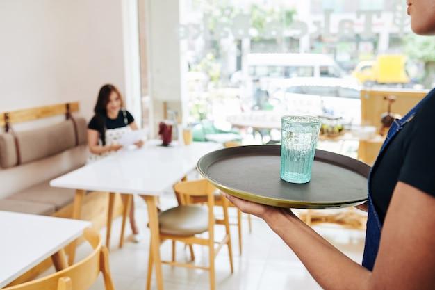 Cameriere che porta l'acqua al cliente