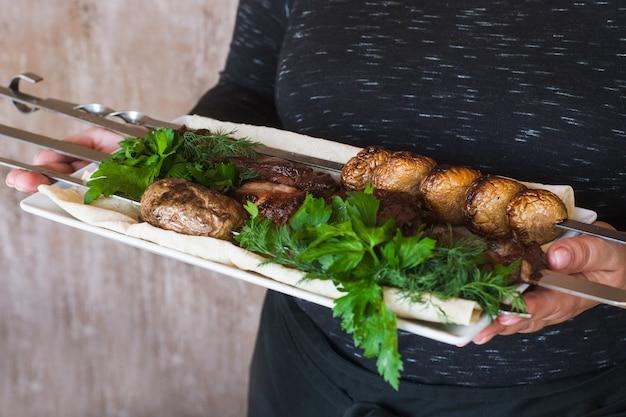 Il cameriere porta shish-kebab con verdure grigliate sul piatto bianco.