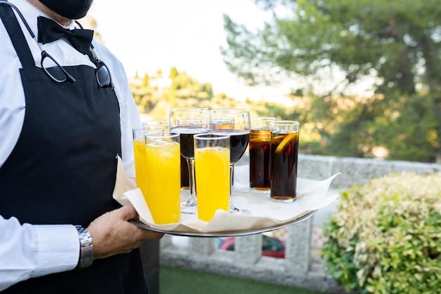 Cameriere che trasportano vassoio con bicchieri con bibite