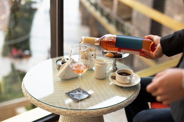 Mano del cameriere che versa vino rosato in vetro