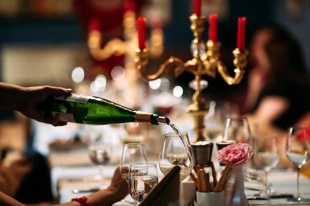Cameriere versando il vino in un bicchiere servito a tavola