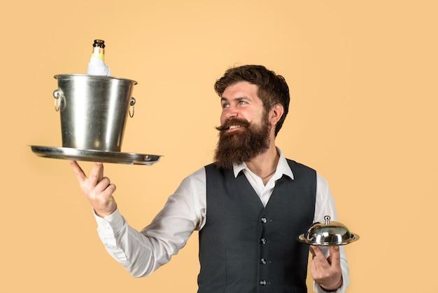 Cameriere bel cameriere con vassoio da portata e refrigeratore per vino ristorante che serve cameriere nel ristorante