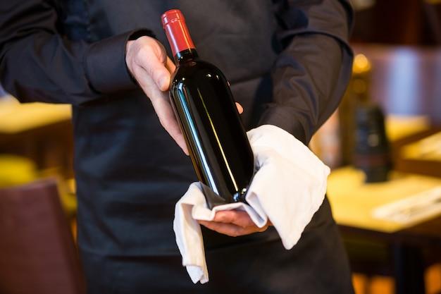 Cameriere che tiene una bottiglia di vino rosso