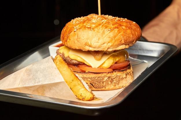 Cameriere che tiene hamburger con carne di manzo, formaggio e patate rustiche