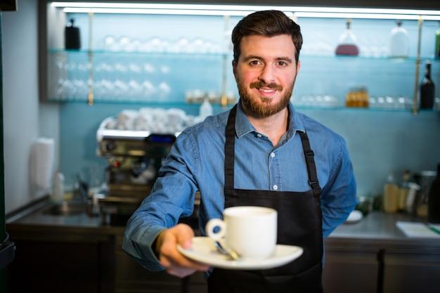 Cameriere che tiene tazza di caffè