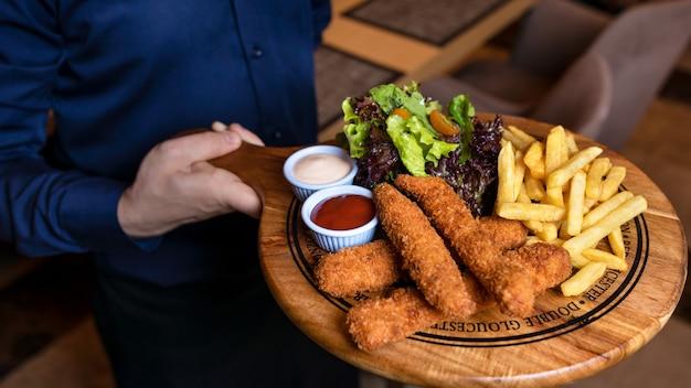 Cameriere che tiene pollo fritto e patatine fritte