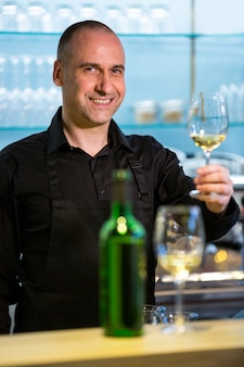 Cameriere che tiene bicchiere di vino bianco