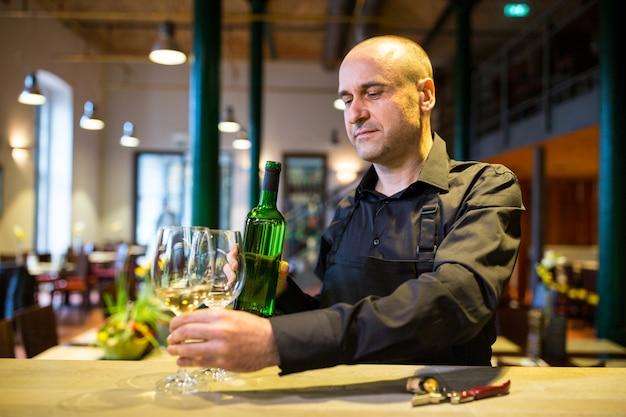 Cameriere che tiene i vetri e una bottiglia di vino bianco