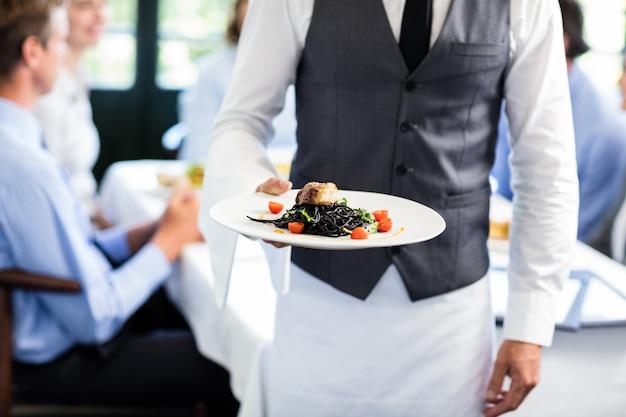 Cameriere che tiene un piatto di pasto