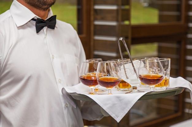 Il cameriere con in mano un vassoio offre agli ospiti dell'evento un bicchiere di whisky e ghiaccio