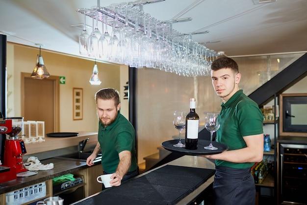 Un cameriere in possesso di un vassoio con una bottiglia di vino e bicchieri nel ristorante bar pub.