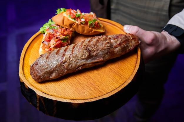 Il cameriere tiene il filetto di vitello con salsa di pomodoro su bruschetta su piatto di legno