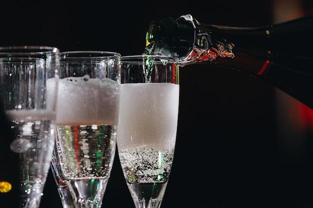 Il cameriere sta versando champagne nei bicchieri champagne