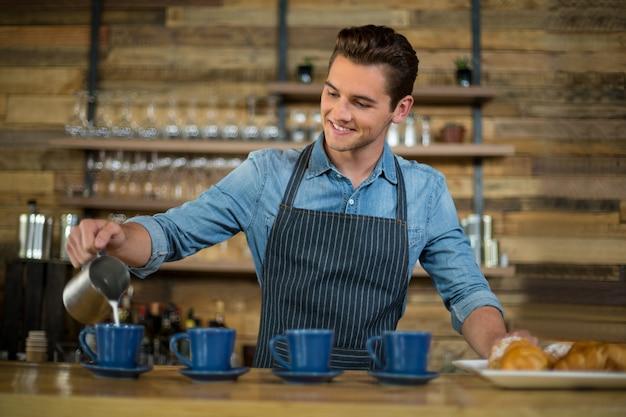 Cameriere che produce tazza di caffè al contatore