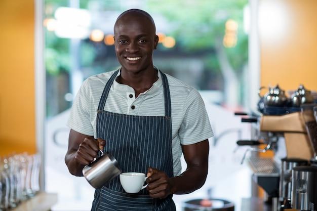 Cameriere che fa tazza di caffè al bancone