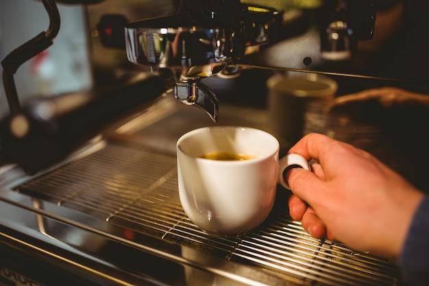 Cameriere che fa una tazza di caffè