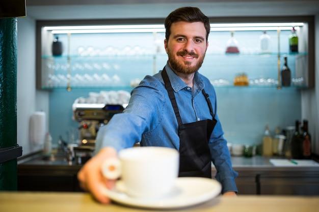 Cameriere che offre tazza di caffè