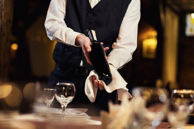 Il cameriere offre ai visitatori vino