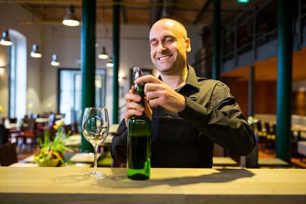 Cameriere che apre una bottiglia di vino bianco