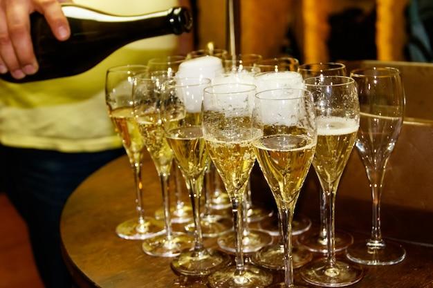Cameriere che versa champagne da una bottiglia nel bicchiere. avvicinamento