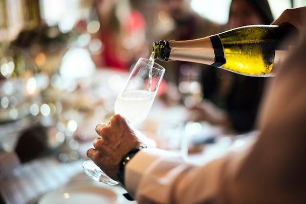 Un cameriere che versa champagne frizzante