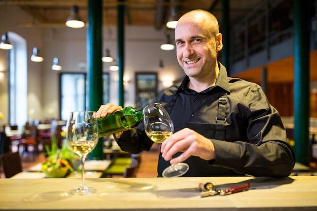 Cameriere che versa vino bianco in vetro