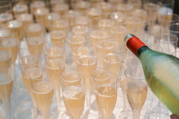 Il cameriere versa lo champagne in una tazza di vino in plastica usa e getta
