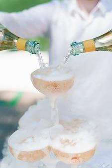 Il cameriere versa lo champagne da 2 bottiglie in bicchieri di cristallo con ghiaccio secco e fumo bianco da vicino