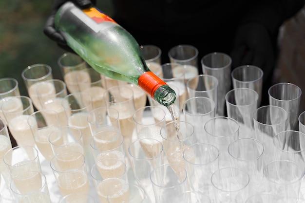 Il cameriere versa lo champagne nel bicchiere di vino