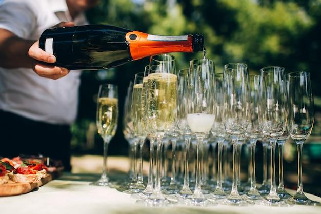 Il cameriere versa lo champagne a una festa. bicchieri di champagne.