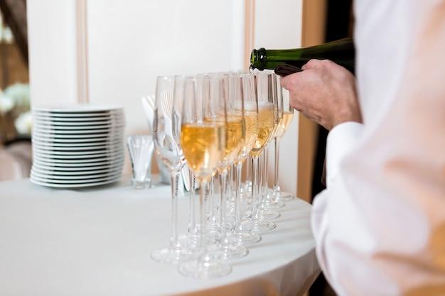 Il cameriere versa lo champagne. fila di bicchieri alla celebrazione