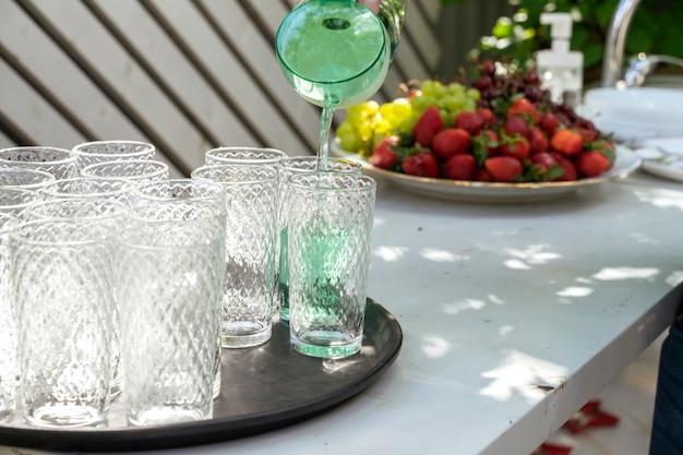 Il cameriere versa le bevande al bicchiere in un banchetto all'aperto fuori sede.
