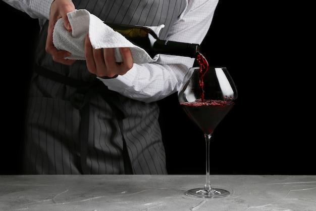 Il cameriere versa il vino in vetro su sfondo scuro