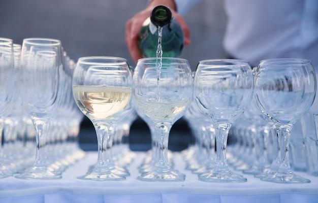 Il cameriere versa il vino in un bicchiere