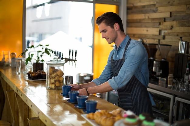 Cameriere che prepara tazza di caffè al contatore
