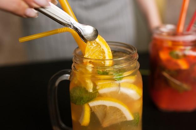 Il cameriere mette il pezzo di arancia a fette in un barattolo di cocktail di frutta.