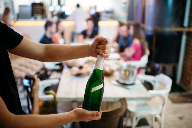 Le mani del cameriere aprono uno champagne