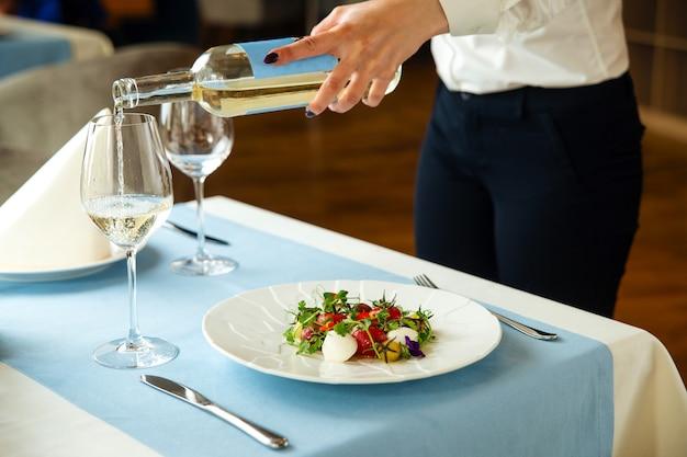 Il cameriere serve il tavolo del ristorante con insalata e vino