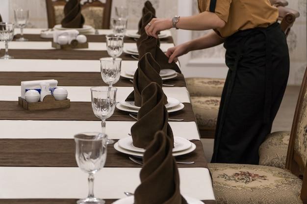 Il cameriere serve un tavolo per banchetti in un lussuoso ristorante