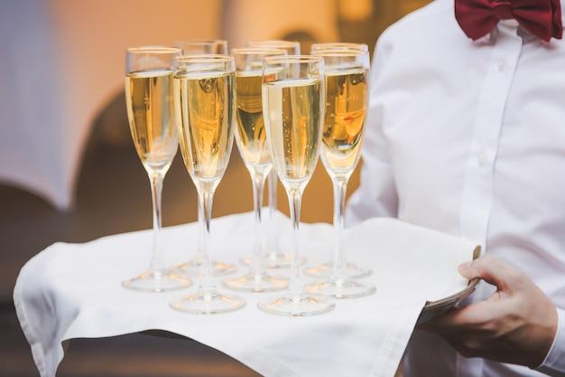 Cameriere che serve bicchieri di champagne su un vassoio in un ristorante.