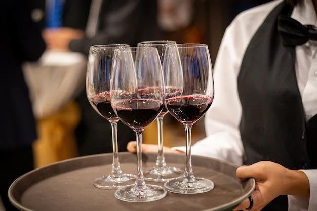 Cameriere che serve un bicchiere di vino rosso