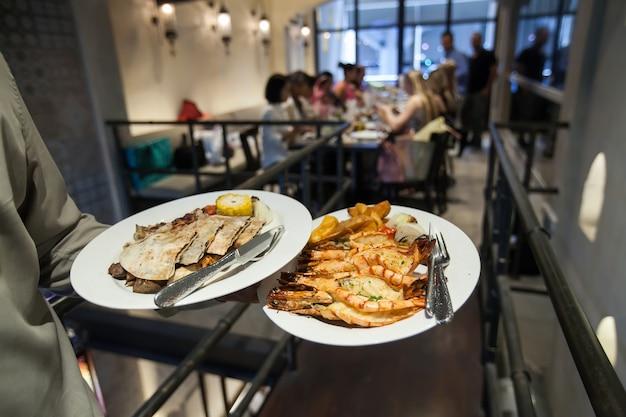 Waiter serving grill gamberetti con cibo india in festa di lusso in ristorante, sfondo blurry.