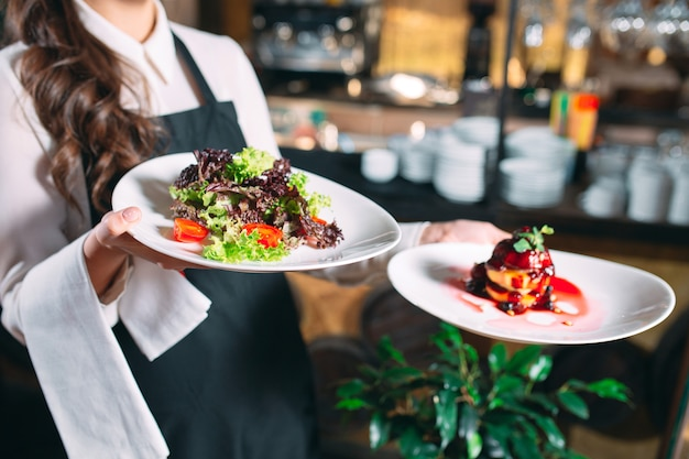 Cameriere che serve in movimento in servizio nel ristorante. il cameriere porta i piatti