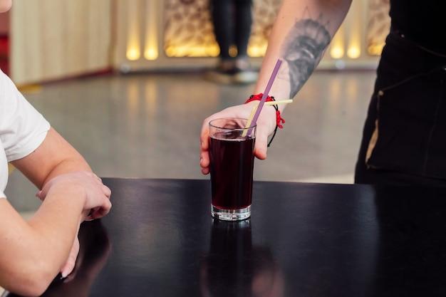 Cameriere che serve un ordine, bevanda rinfrescante o succo di frutta