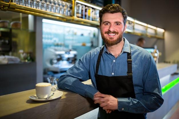 Cameriere in piedi al bancone con una tazza di caffè