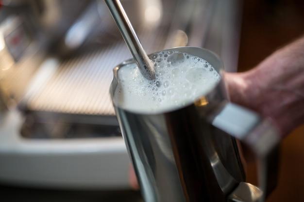 Cameriere a vapore latte alla macchina per il caffè