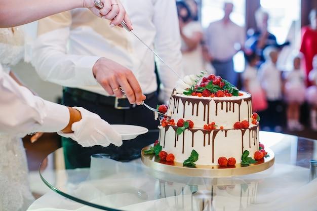 Il cameriere prende un pezzo di torta nuziale mentre la sposa e lo sposo lo tagliano